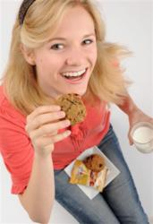 Teenage girl eating an Omega Cookie with a glass of milk